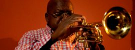 Black man wearing a red plaid shirt and playing trumpet on a red background